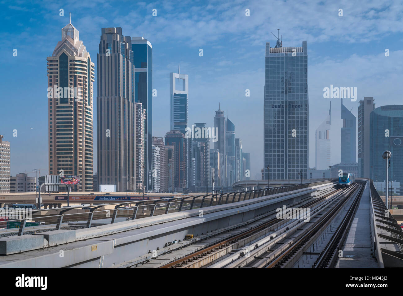 Tall buildings and the Metro train track in downtown Dubai, UAE, Middle East. - Stock Image