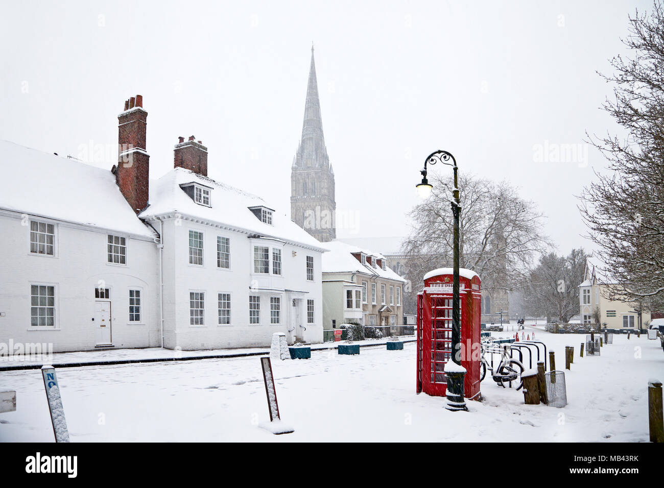 A telephone box amidst snow in the cathedral close in Salisbury in Wiltshire. - Stock Image