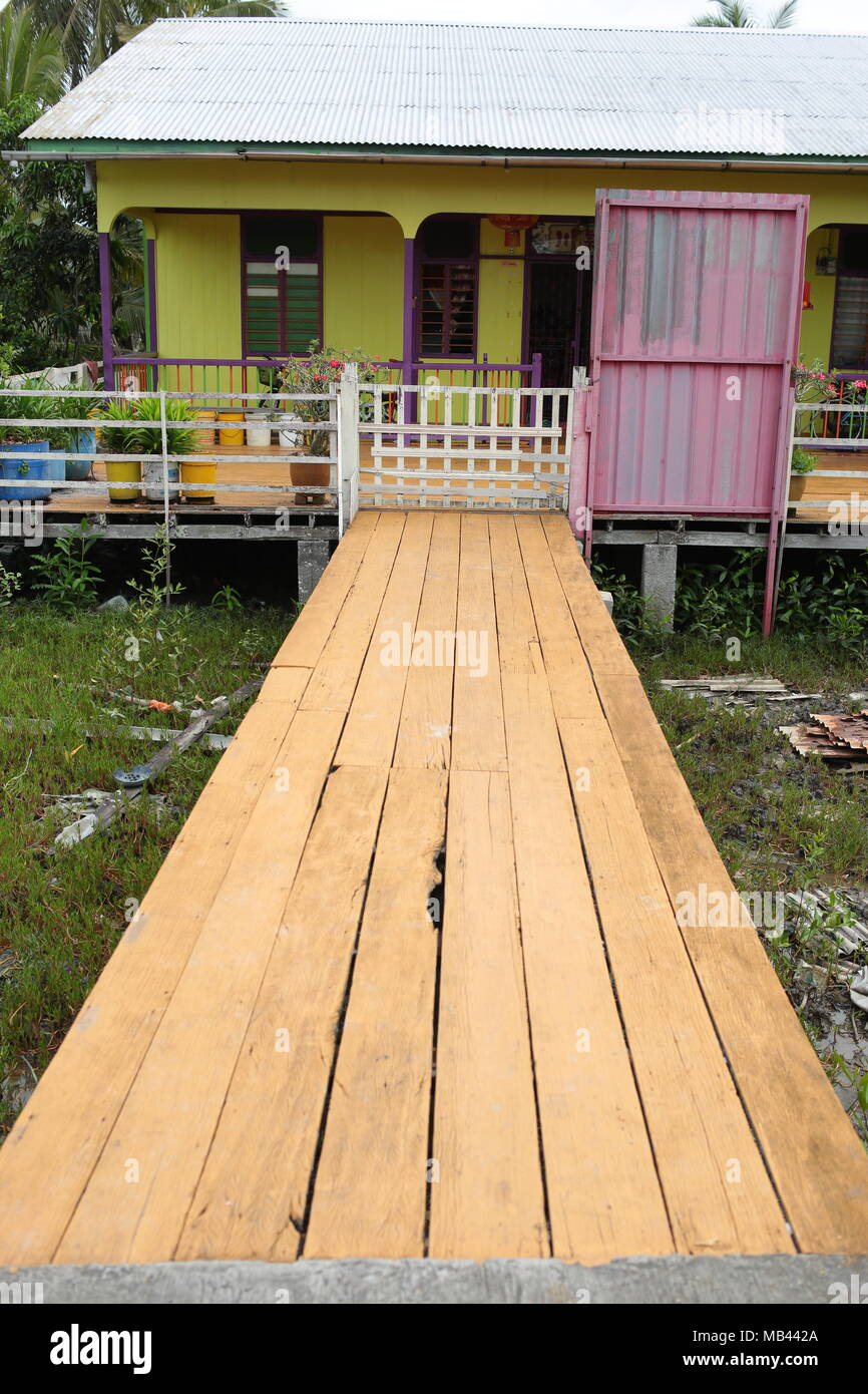 A newly painted civilian home and wooden walkway at Crab island, a famous fishing village in Malaysia. - Stock Image