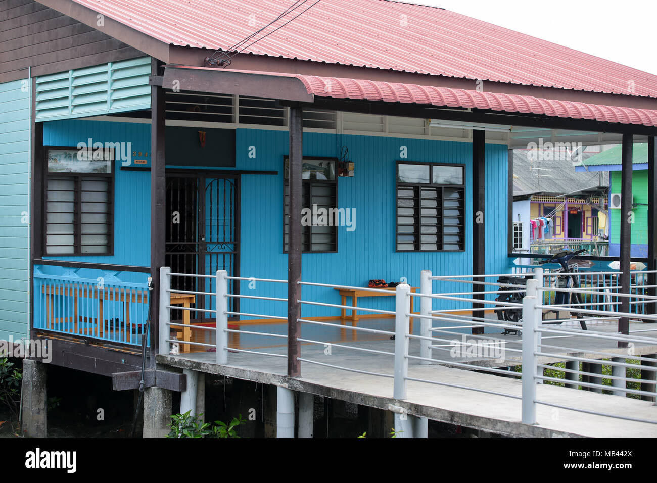 A newly painted civilian home with concrete walkway at Crab island, a famous fishing village in Malaysia. - Stock Image
