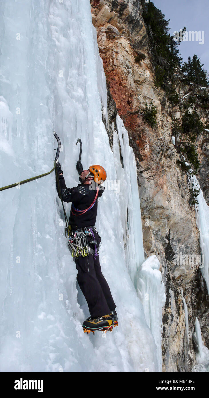 male ice climber on a steep frozen waterfall on a beautiful winter day in the Swiss Alps - Stock Image