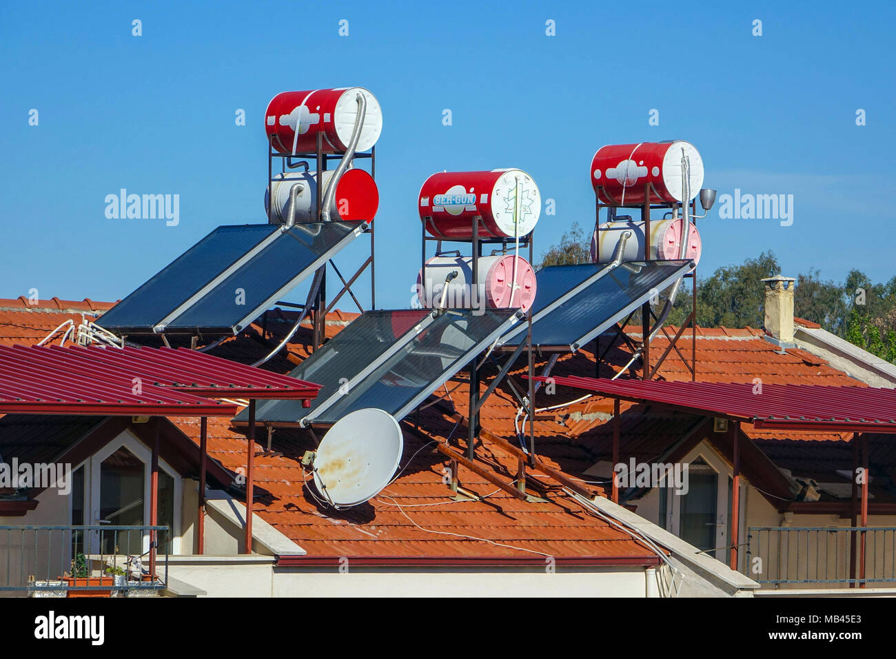 Solar panels and red water tanks on rooftop, Fethiye, Turkey - Stock Image