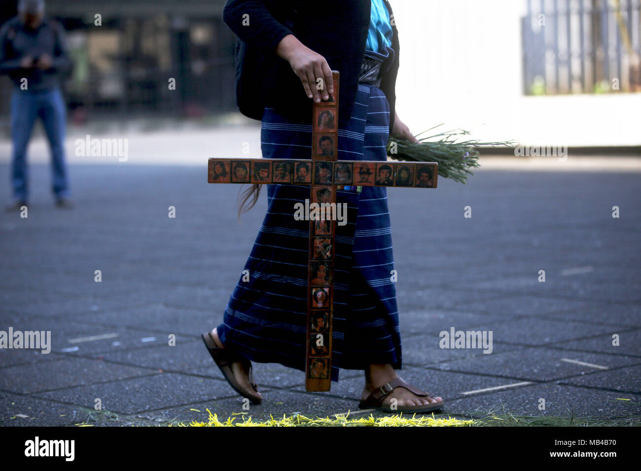 A woman holds a wooden cross with the portraits of victims of the dictatorship at an altar in Guatemala City, Guatemala, 06 April 2018. Civil organizations and relatives of the victims of the internal armed conflict during the government of Jose Efrain Rios Montt payed tribute to the victims of the ixil genocide at the Palace of Justice. The court in charge of the case decided to close the criminal process against the former dictator, who died past Sunday at the age of 91, and to give the families an economic compensarion of 67,567 dollars. EFE/Esteban Biba - Stock Image