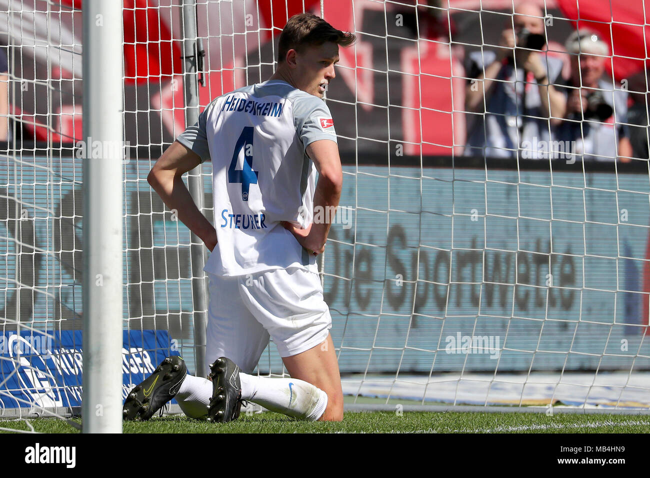 07 April 2018, Germany, Nuremberg, Soccer: 2nd Bundesliga, 1. FC Nuremberg vs 1. FC Heidenheim, in the Max Morlock Stadium. Heidenheim's Oliver Steurer kneeling on the grass after Nuremberg's scoring of the 3:1. Photo: Daniel Karmann/dpa - IMPORTANT NOTICE: Due to the German Football League·s (DFL) accreditation regulations, publication and redistribution online and in online media is limited during the match to fifteen images per match - Stock Image
