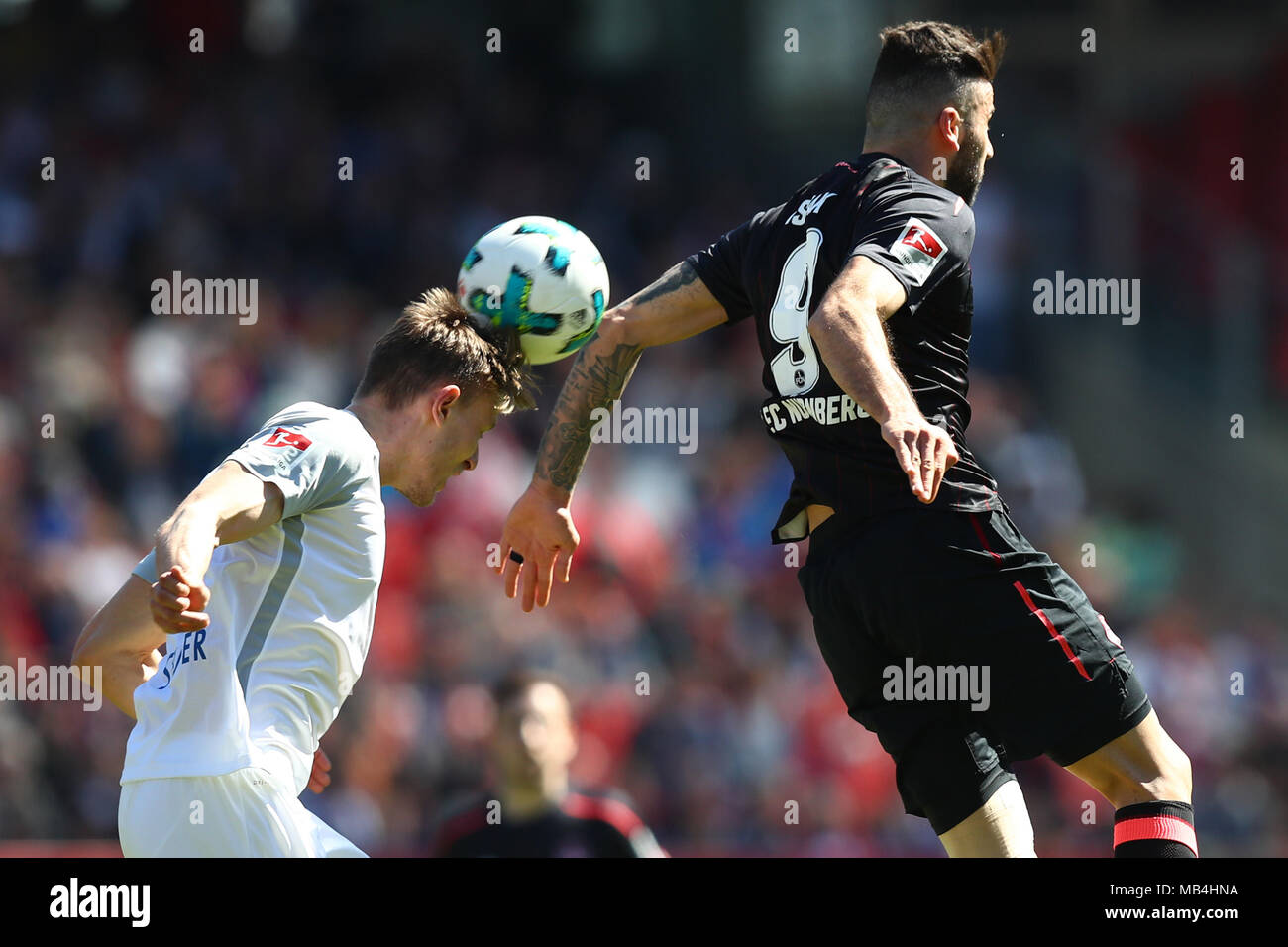 07 April 2018, Germany, Nuremberg, Soccer: 2nd Bundesliga, 1. FC Nuremberg vs 1. FC Heidenheim, in the Max Morlock Stadium. Nuremberg's Mikael Ishak (R) and Heidenheim's Oliver Steurer vying for the ball. Photo: Daniel Karmann/dpa - IMPORTANT NOTICE: Due to the German Football League·s (DFL) accreditation regulations, publication and redistribution online and in online media is limited during the match to fifteen images per match - Stock Image