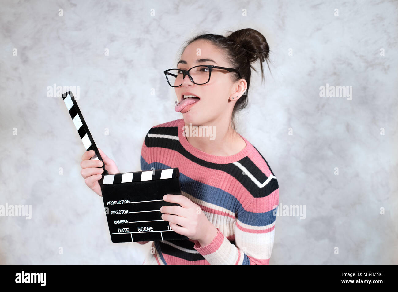 Young woman actress comedy funny grimace face expression mouth open with movie clapper board - Stock Image