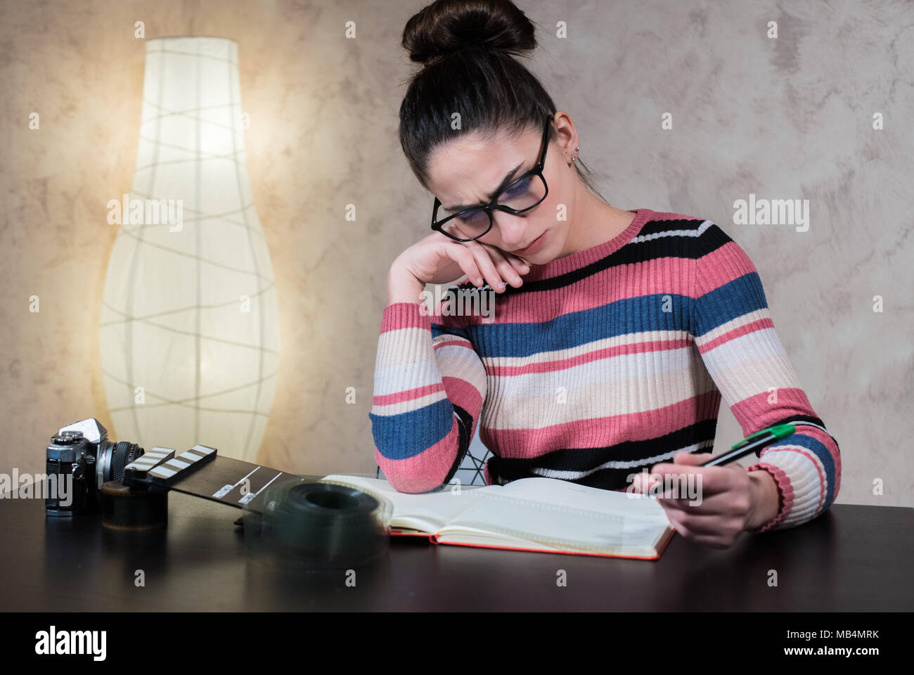 Young attractive woman thoughtful working writing script with movie objects on desktop - Stock Image