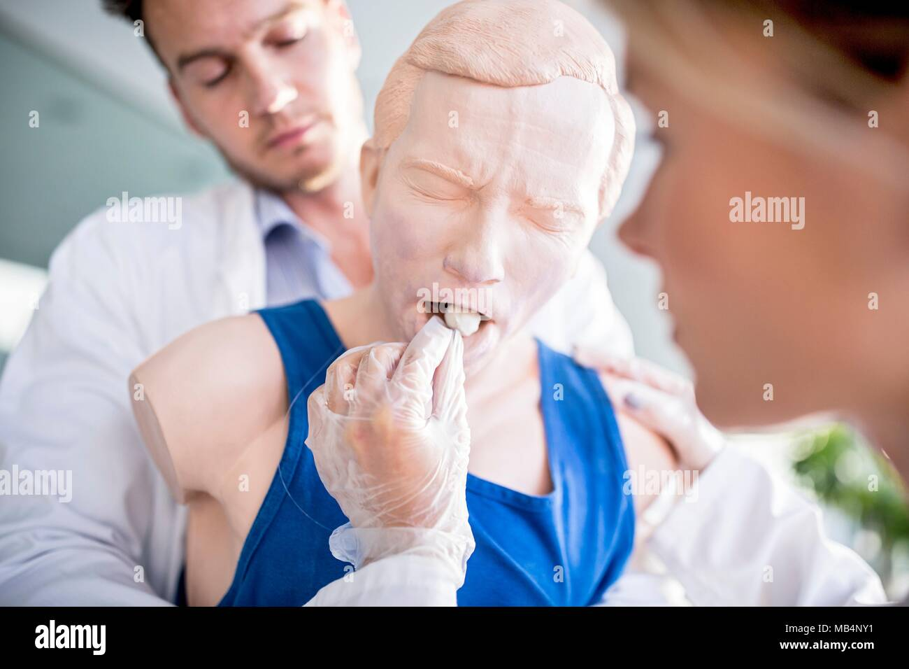 Doctor practising the Heimlich manoeuvre on a training dummy. - Stock Image