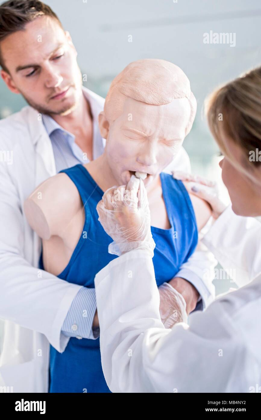 Doctor practising the Heimlich manoeuvre on a training dummy. Stock Photo