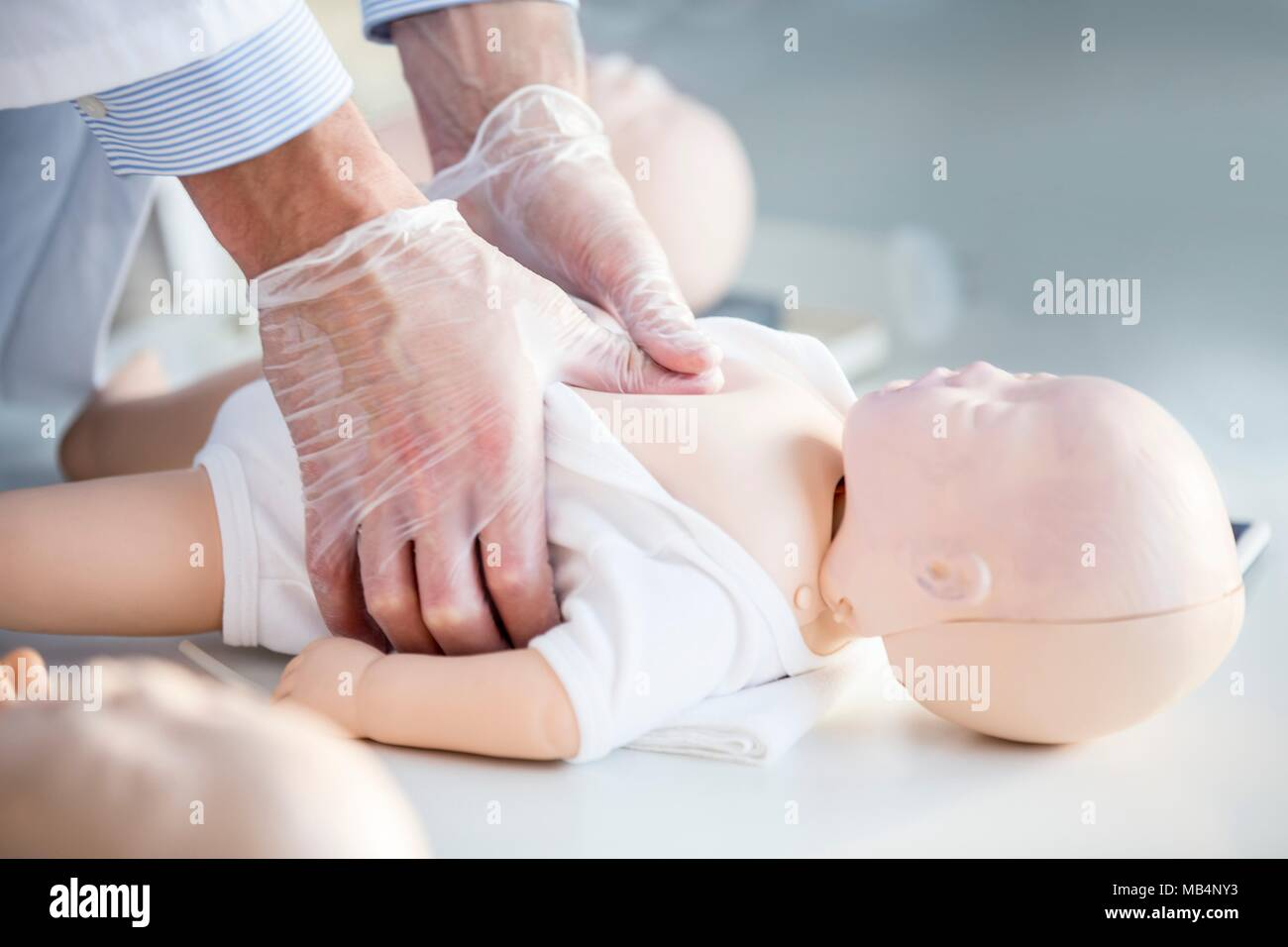 Doctor practising chest compressions on an infant CPR training dummy. - Stock Image