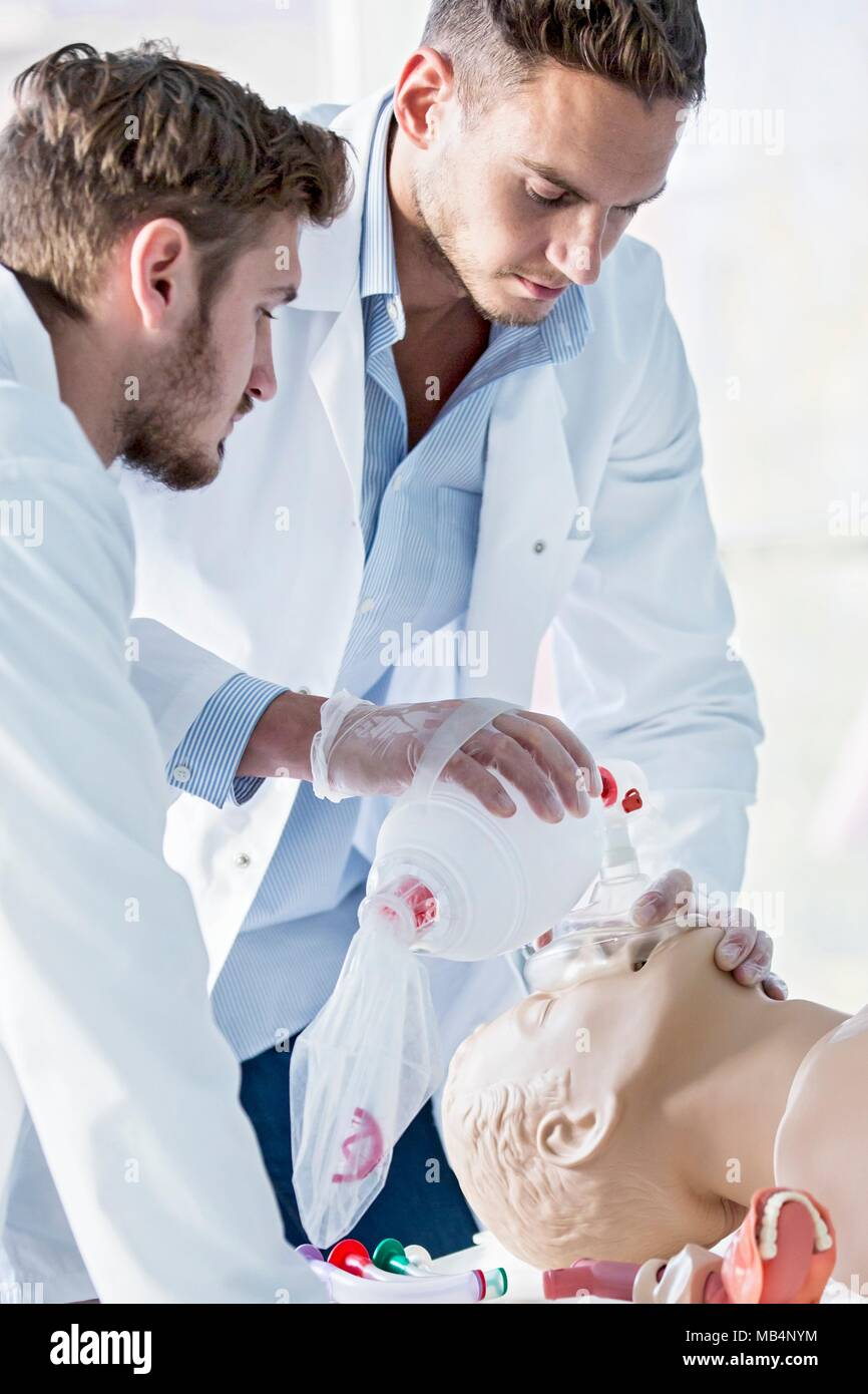 MODEL RELEASED. Doctor practising bag-valve-mask ventilation on a training dummy. - Stock Image