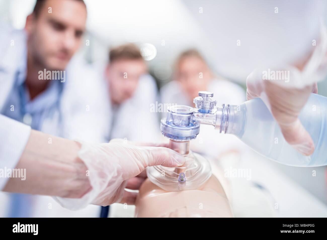 MODEL RELEASED. Doctor practising bag-valve-mask ventilation on a training dummy. - Stock Image
