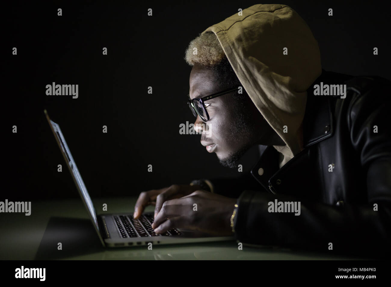 Handsome Afro American man using a laptop browse in internet till late - Stock Image