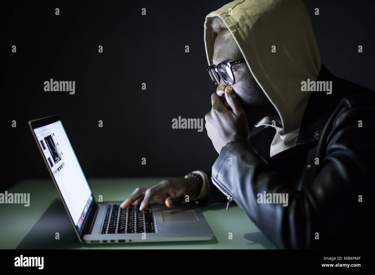 Afro American Man Sits At Night At A Computer Desk Using The Internet Gamer Sits At Night At A Table Near A Computer With Cookies In His Hands And Lo Stock Photo