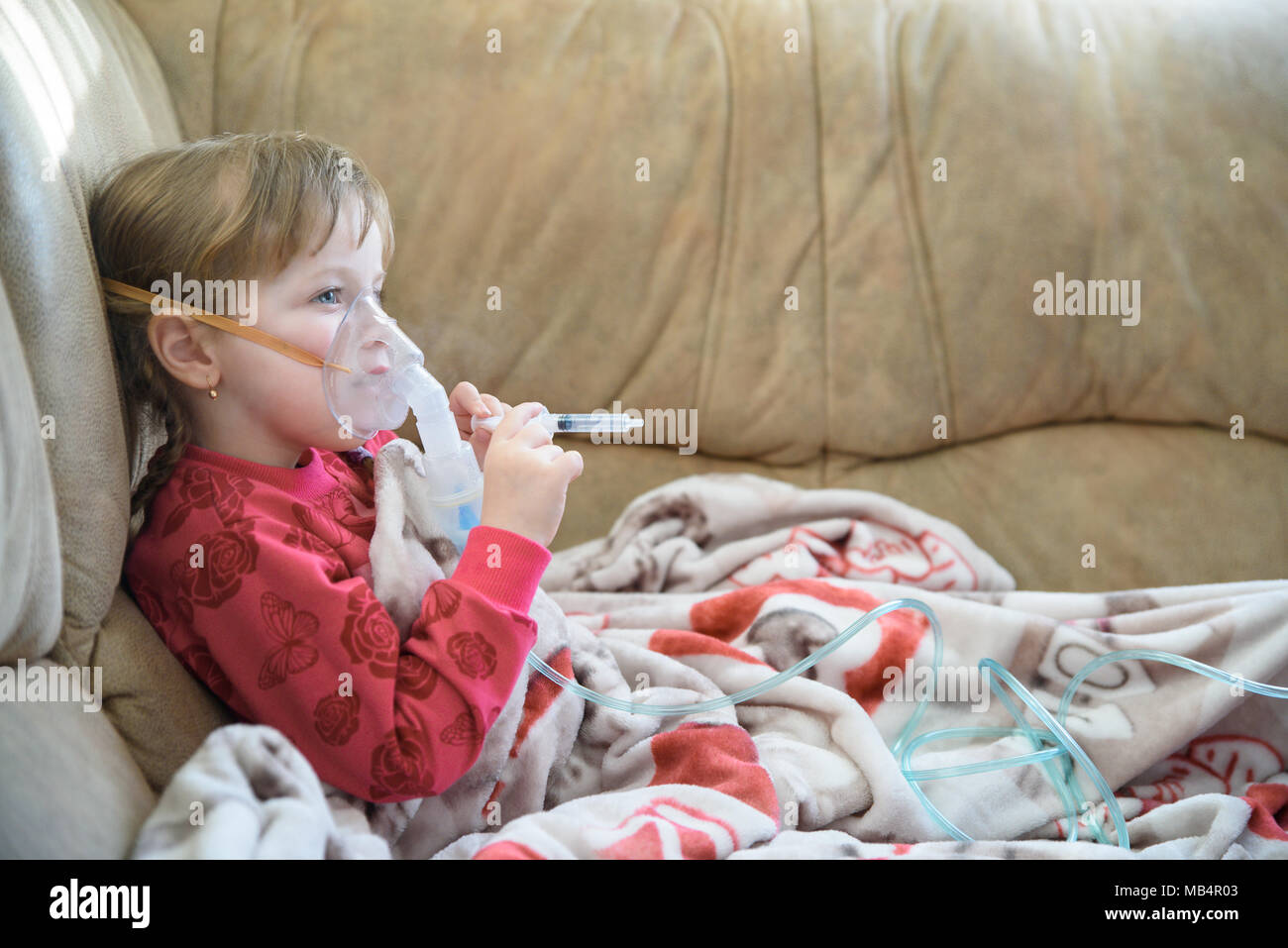 Little girl in a mask, cough treatment using a nebulizer at home - Stock Image