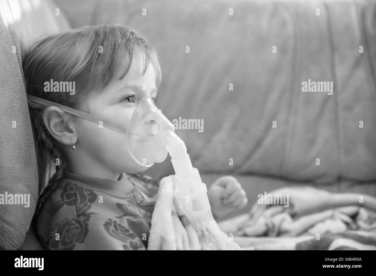 Little girl in a mask, treatments respiratory diseases with a nebulizer at home - Stock Image