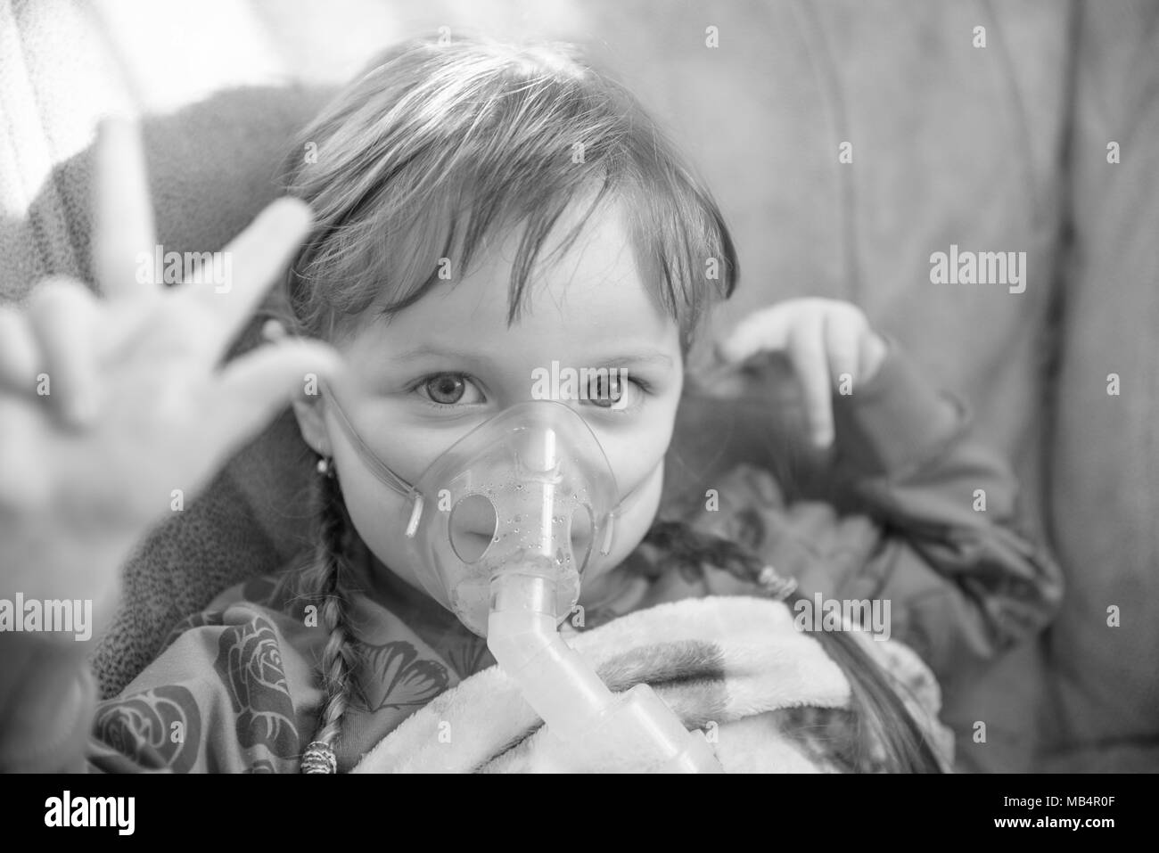 Little girl in a mask, treatments respiratory tract with a nebulizer at home - Stock Image
