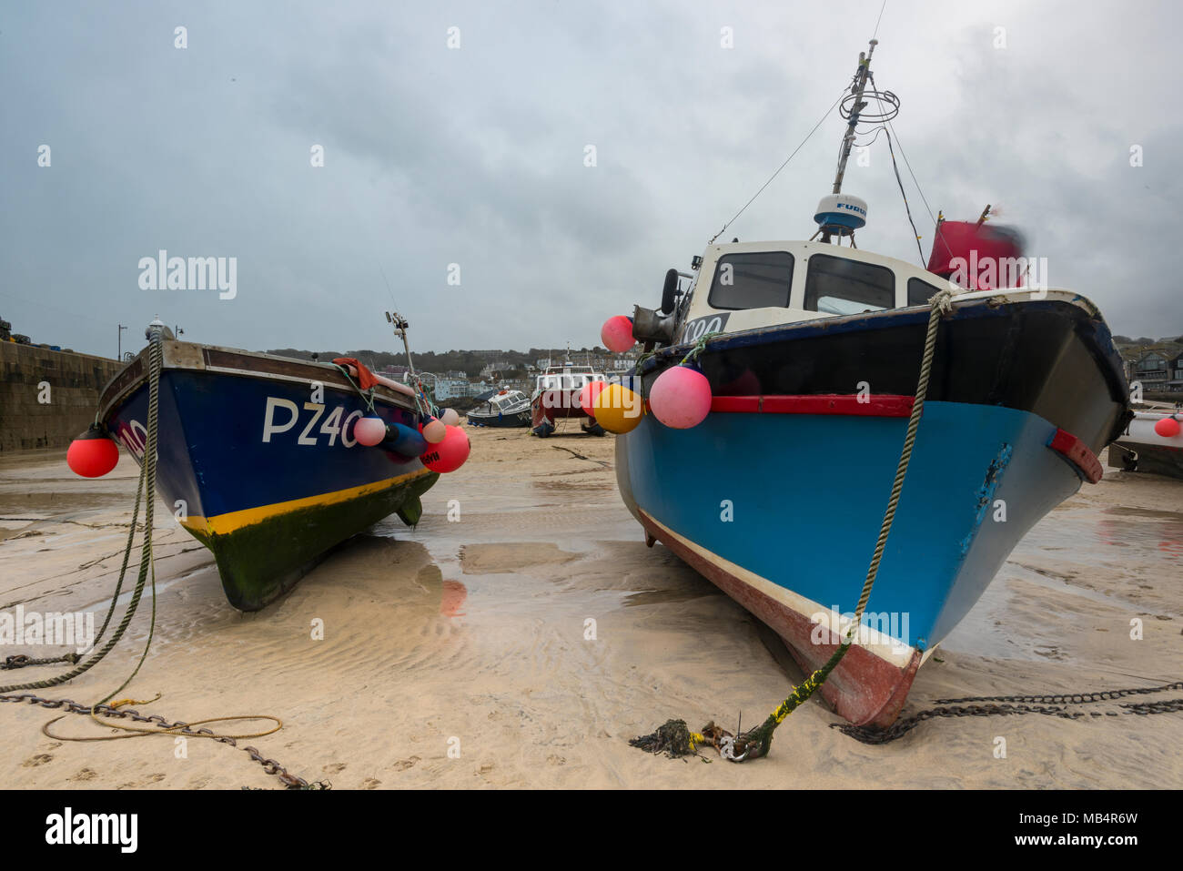 Fishing boats on the beach in the harbour at st Ives in west cornwall high and dry at low tide. Fishermen leaving boats and trawlers on the beach. Stock Photo