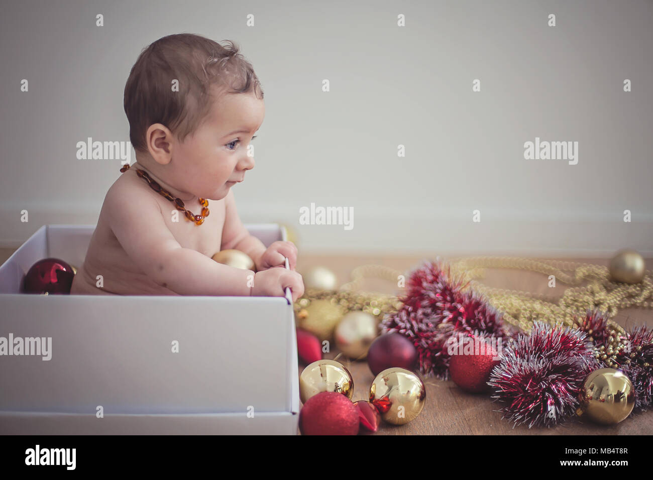 6 month old baby in a box with christmas decorations - Stock Image