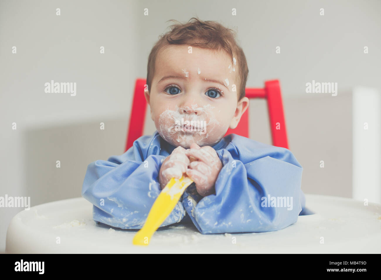 6 month old baby boy feeding himself yoghurt with a spoon - Stock Image