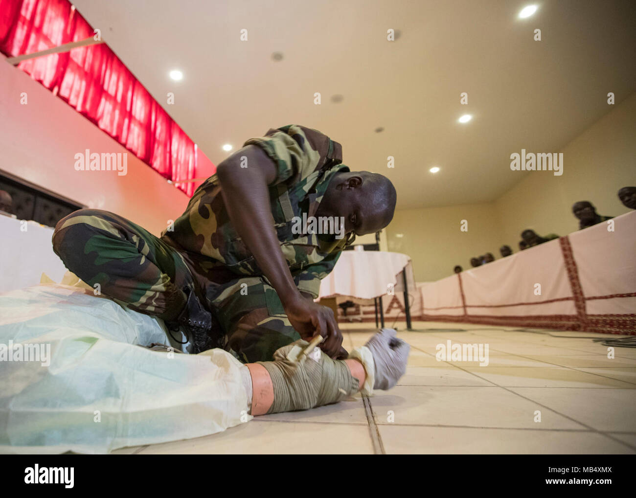 Cpl. Birame Faye, infirmier with the Senegalese Army, demonstrates pre-hospital trauma care during a timed scenario at a workshop taught by U.S. Army medical personnel at Base Militaire Bel Air, Senegal, during MEDRETE 18-1, Feb. 20, 2018. MEDRETE is a combined effort between the Senegalese government, U.S. Army Africa, and the Vermont National Guard. MEDRETE 18-1 is the first in a series of medical readiness training exercises that U.S. Army Africa is scheduled to facilitate within various countries in Africa, and serves as an opportunity for the partnered militaries to hone and strengthen th - Stock Image