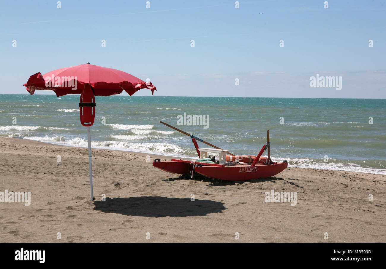Red beach rescue boat and a the watcher's umbrella corner - Stock Image