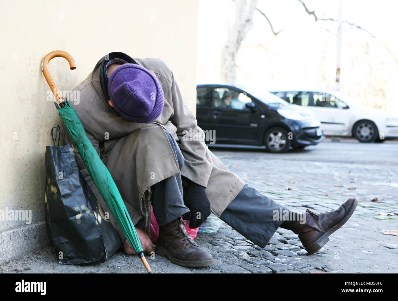 Homeless with hat, umbrella, and bag sleeping in the street in a plastic position - Stock Image