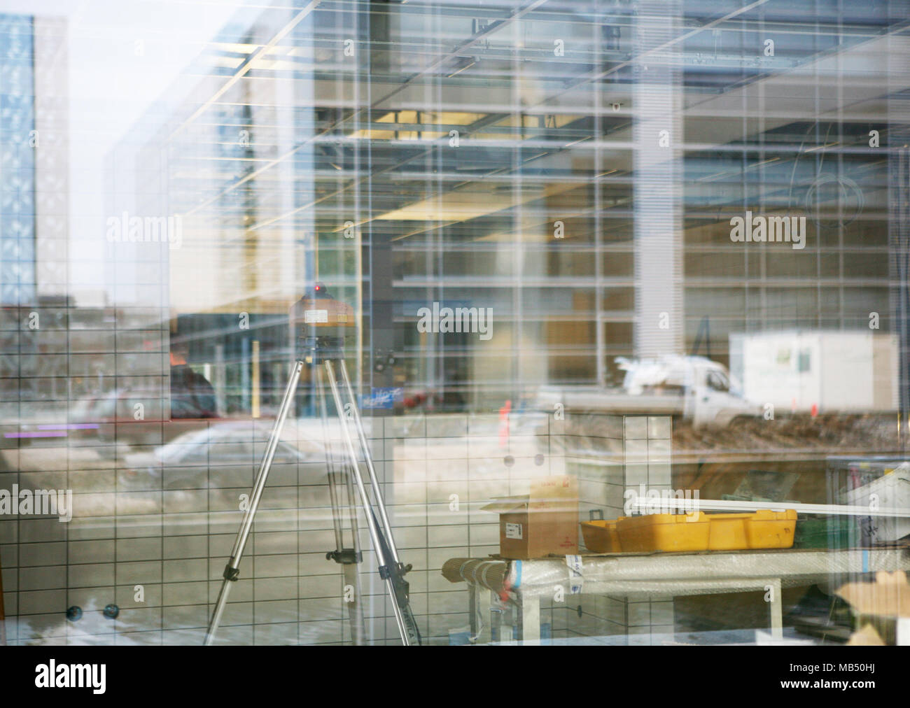 Reflex glass building construction site with tripod and helmet - Stock Image