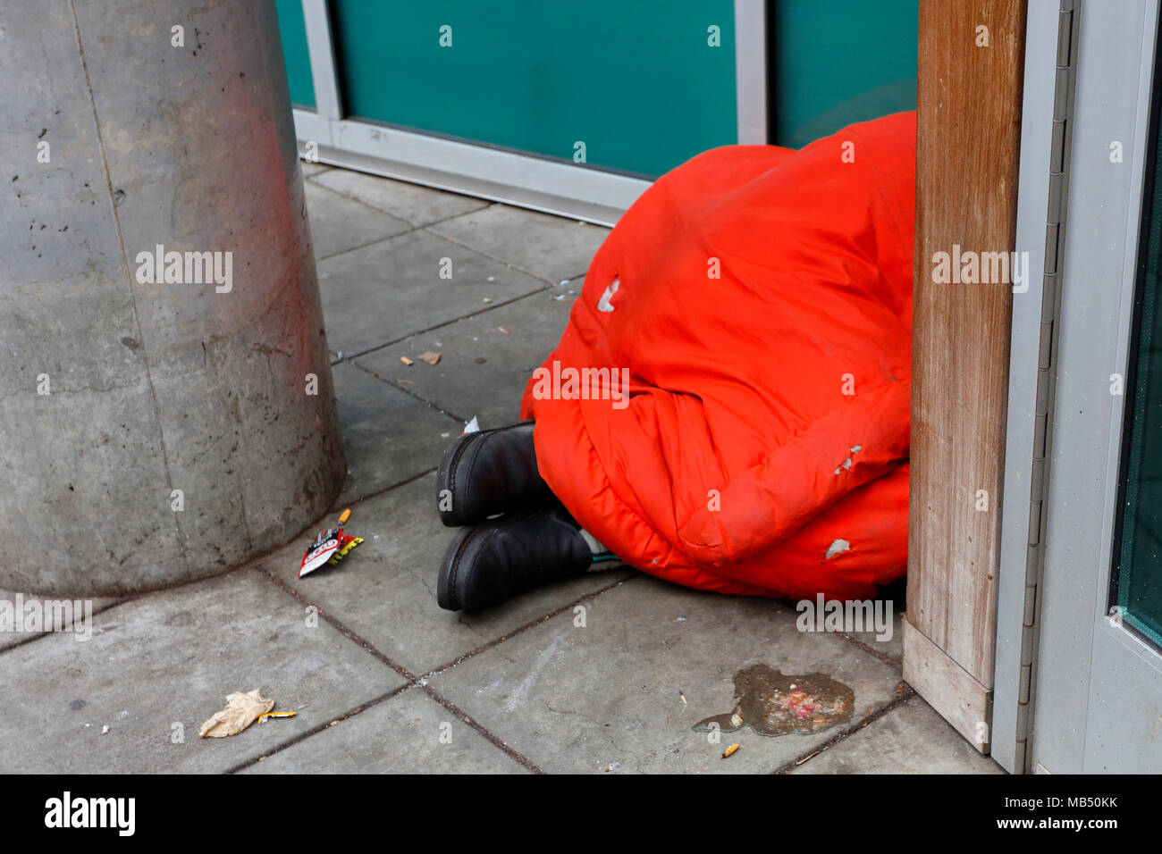 A homeless person under a sleeping bag in downtown - Stock Image