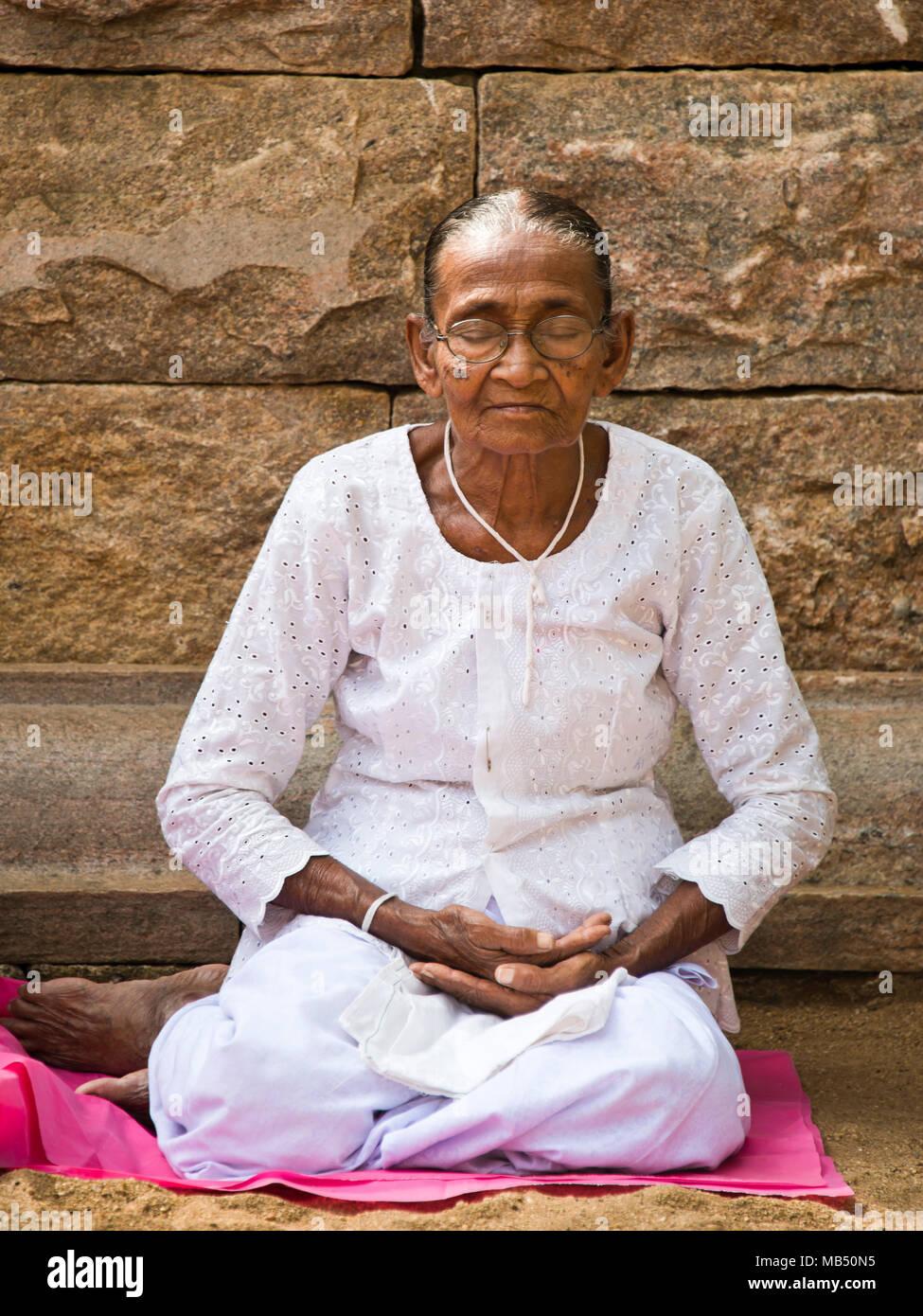 Vertical portrait of an old lady meditating at Jaya Sri Maha Bodhi in Anuradhapura, Sri Lanka. Stock Photo