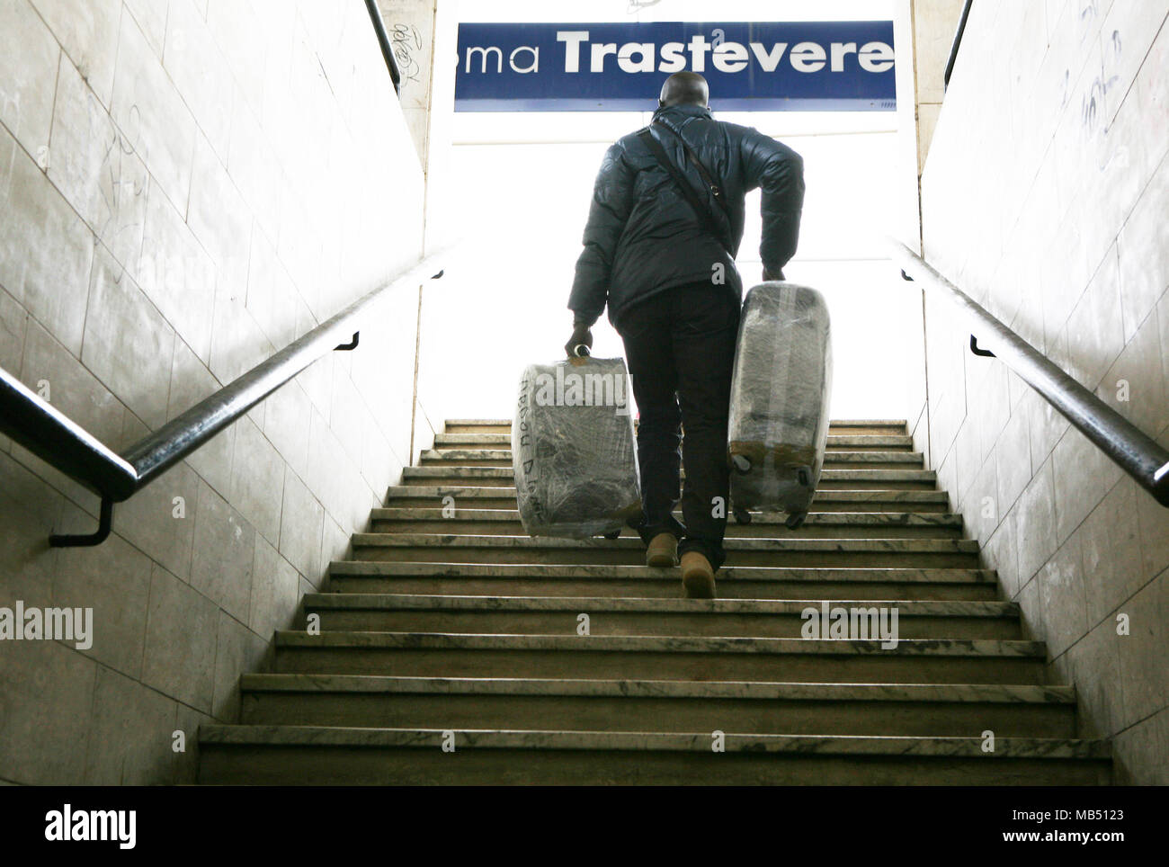 Passenger climbing up the stair with luggage at Trastevere railway station, Rome, Italy - Stock Image