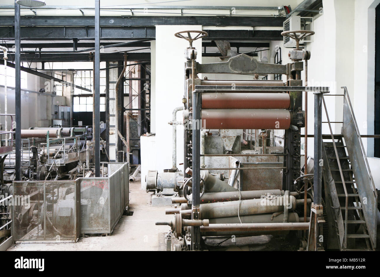 Old run down industrial plant machinery with cogs and gear wheels - Stock Image