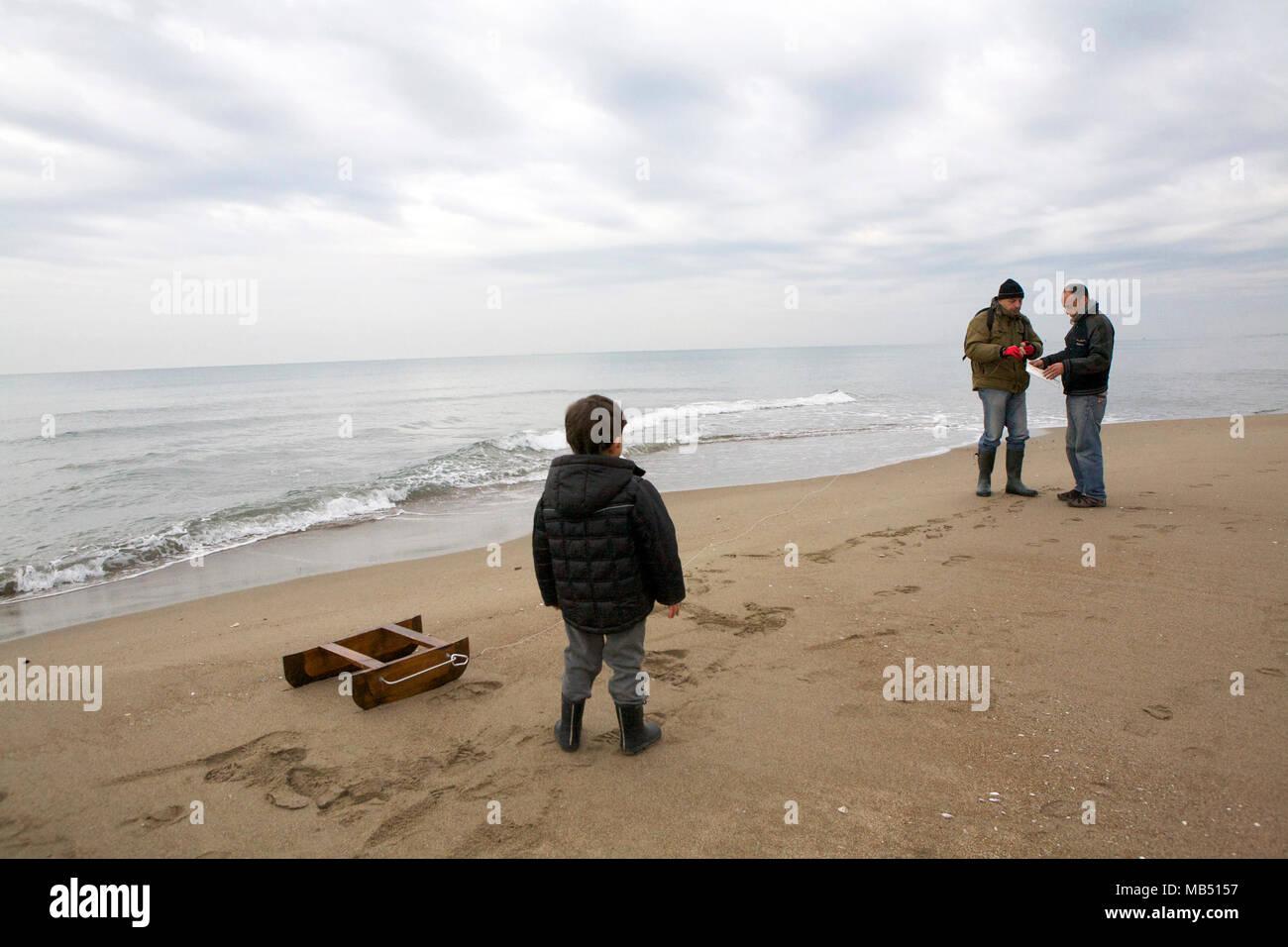 Little boy staring in wonder at fishermen on the beach, Lavinio, Italy - Stock Image