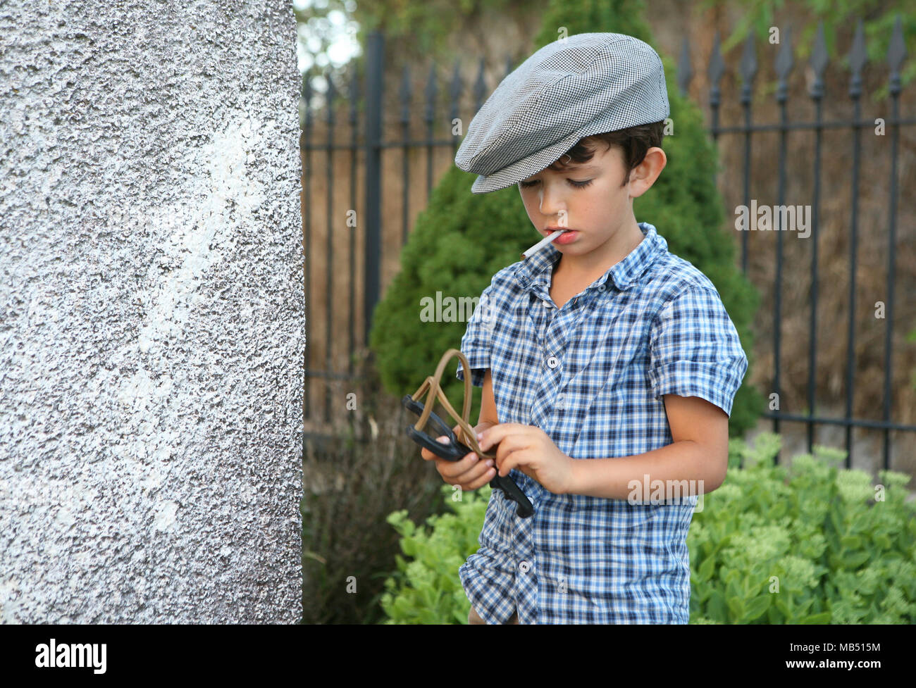Boy with sigarette and coppola hat prepares to shot with the sling, Italy - Stock Image