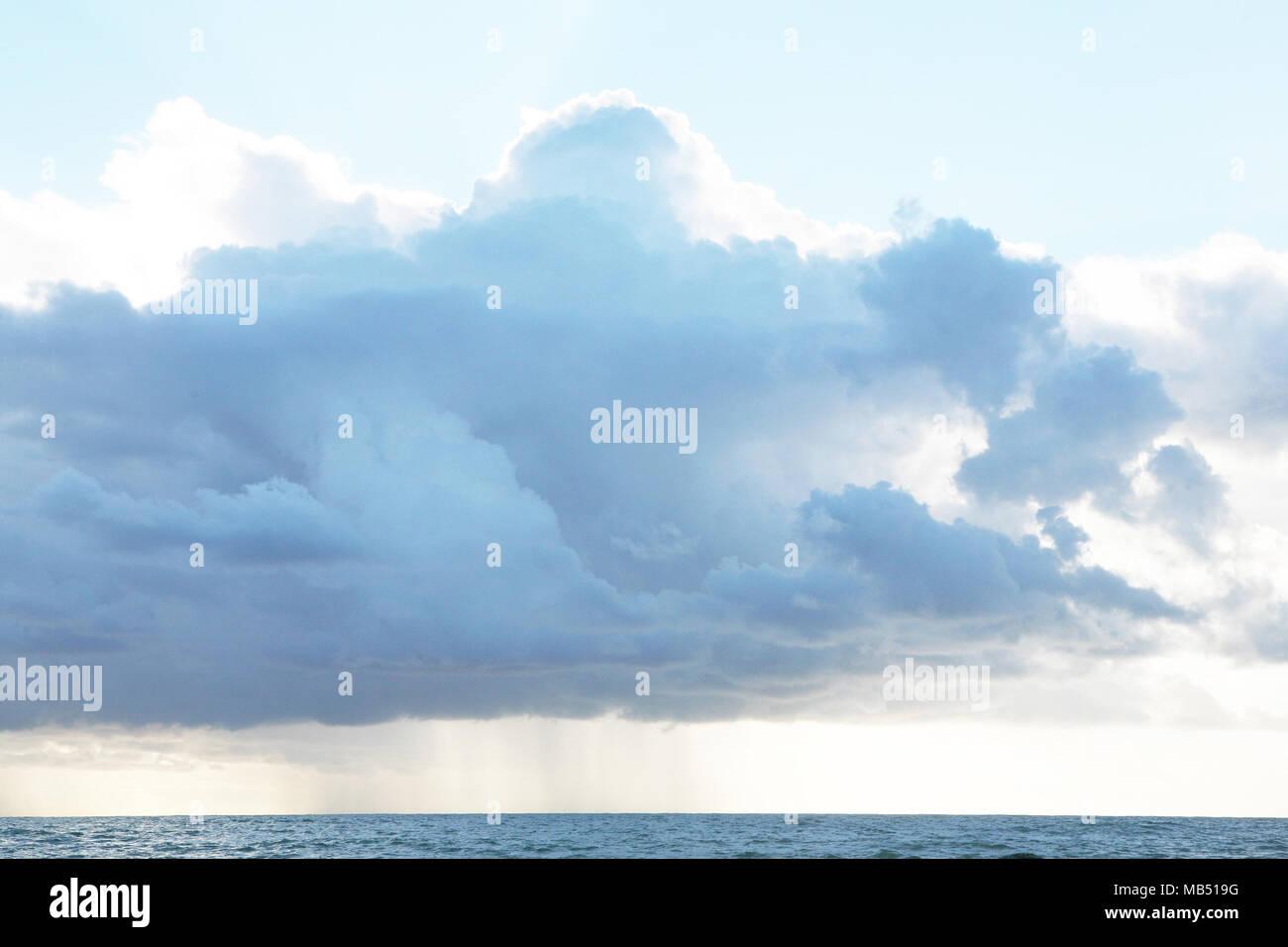 Storm rain cloud and sun over the sea - Stock Image