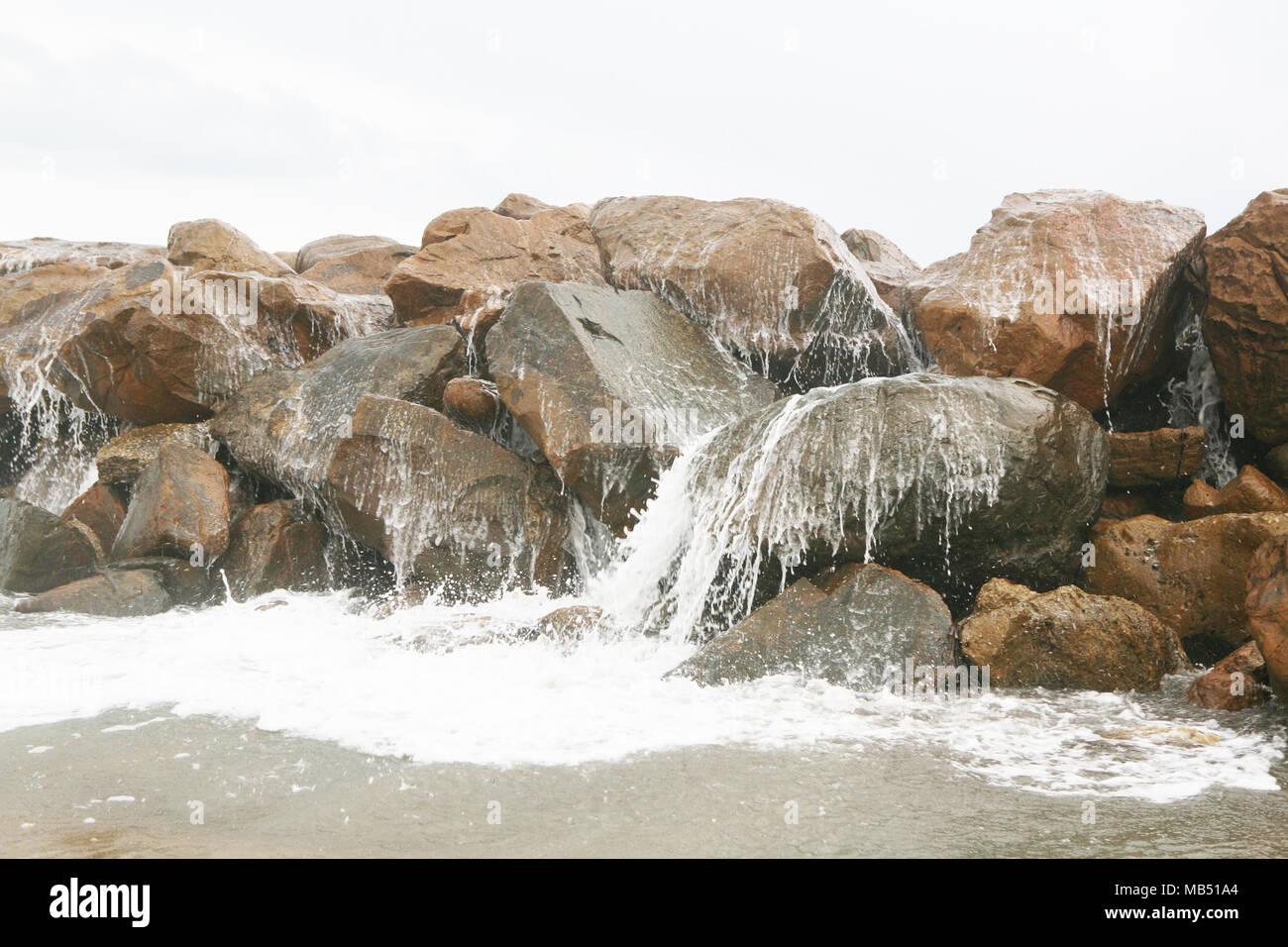 Sea wave breaking on the rocks - Stock Image