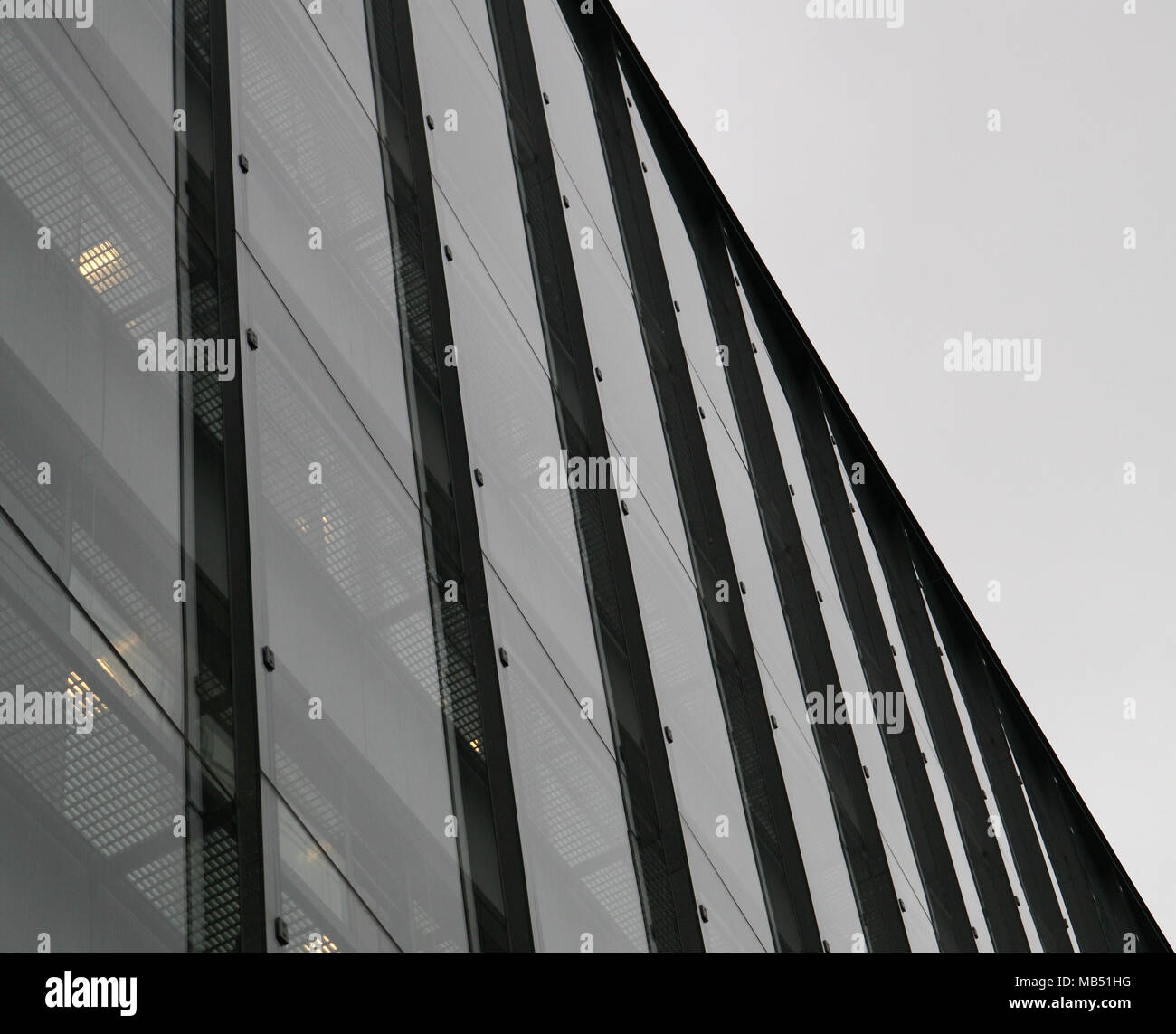 Glass and steel building facade on overcast sky - Stock Image
