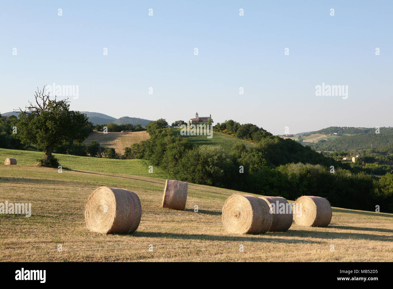 Countryside landscape with round staw bails and small church - Stock Image