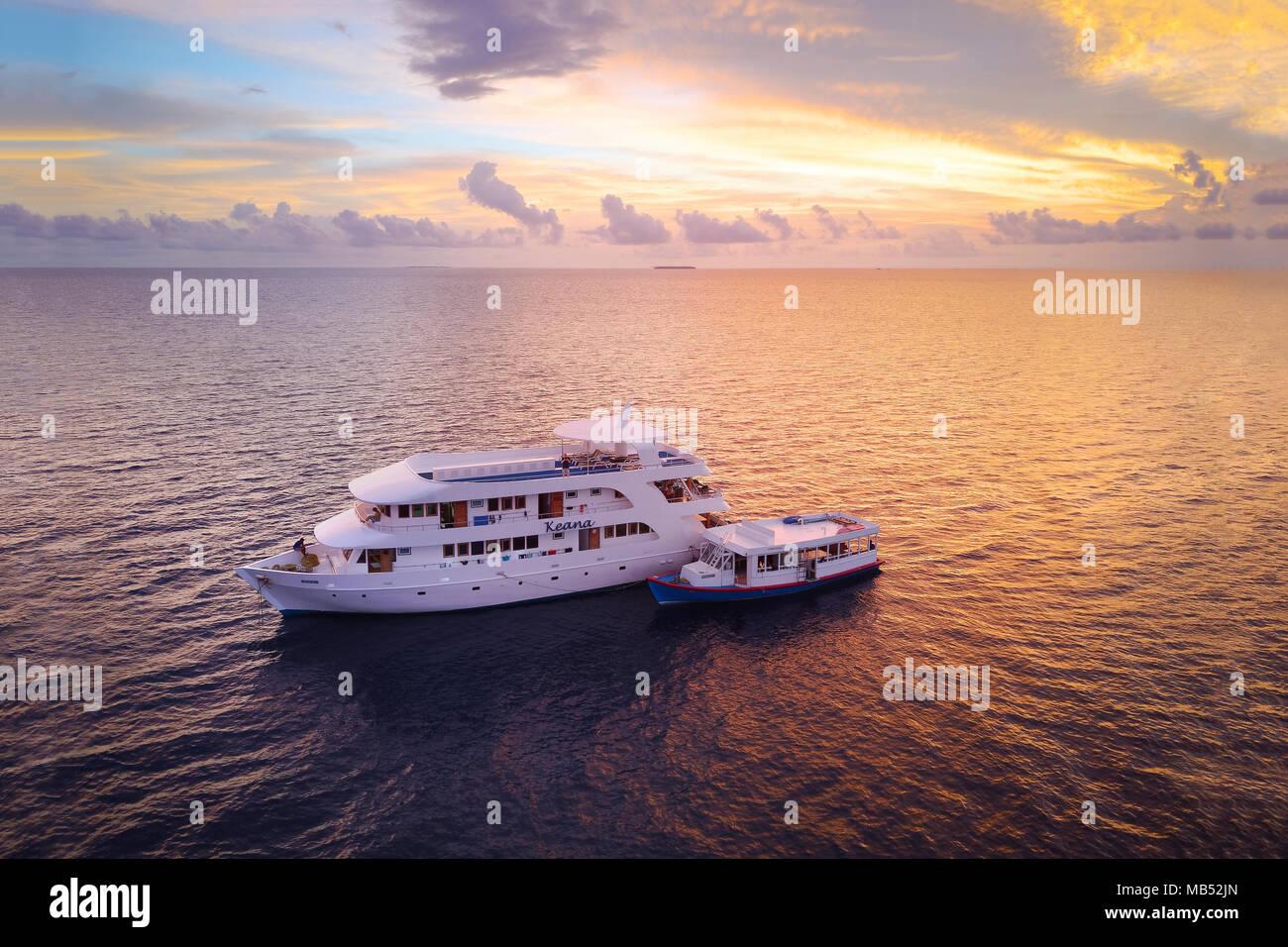 Diving safari ship MS Keana with diving dhoni anchored at sunset, Ari Atoll, Indian Ocean, Maldives - Stock Image