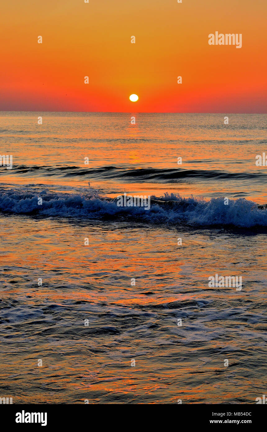 Early mornings waves with sunrise - Stock Image