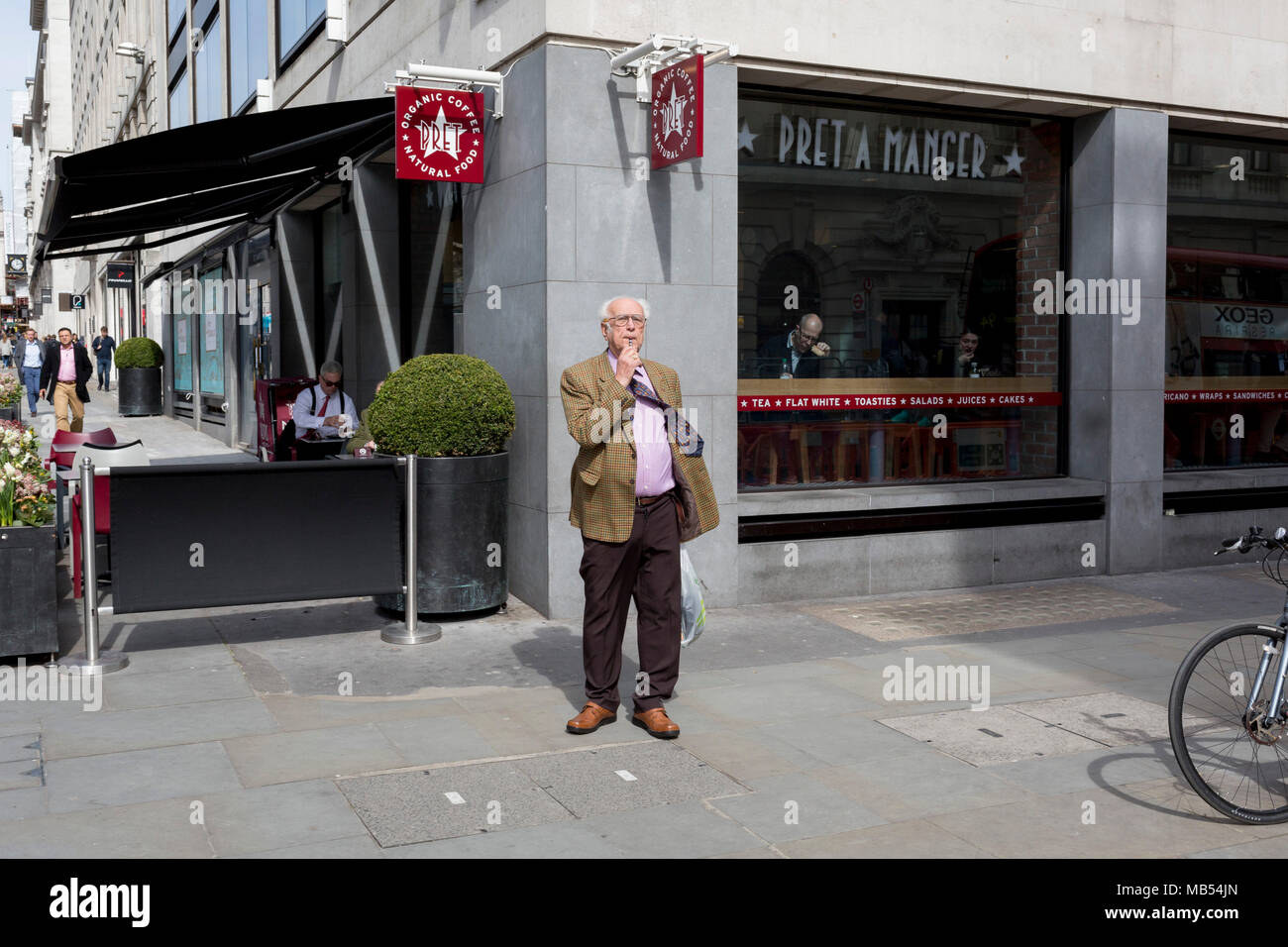 An elderly man vapes on the corner of a central London street, on 6th April 2018, in London, England. - Stock Image