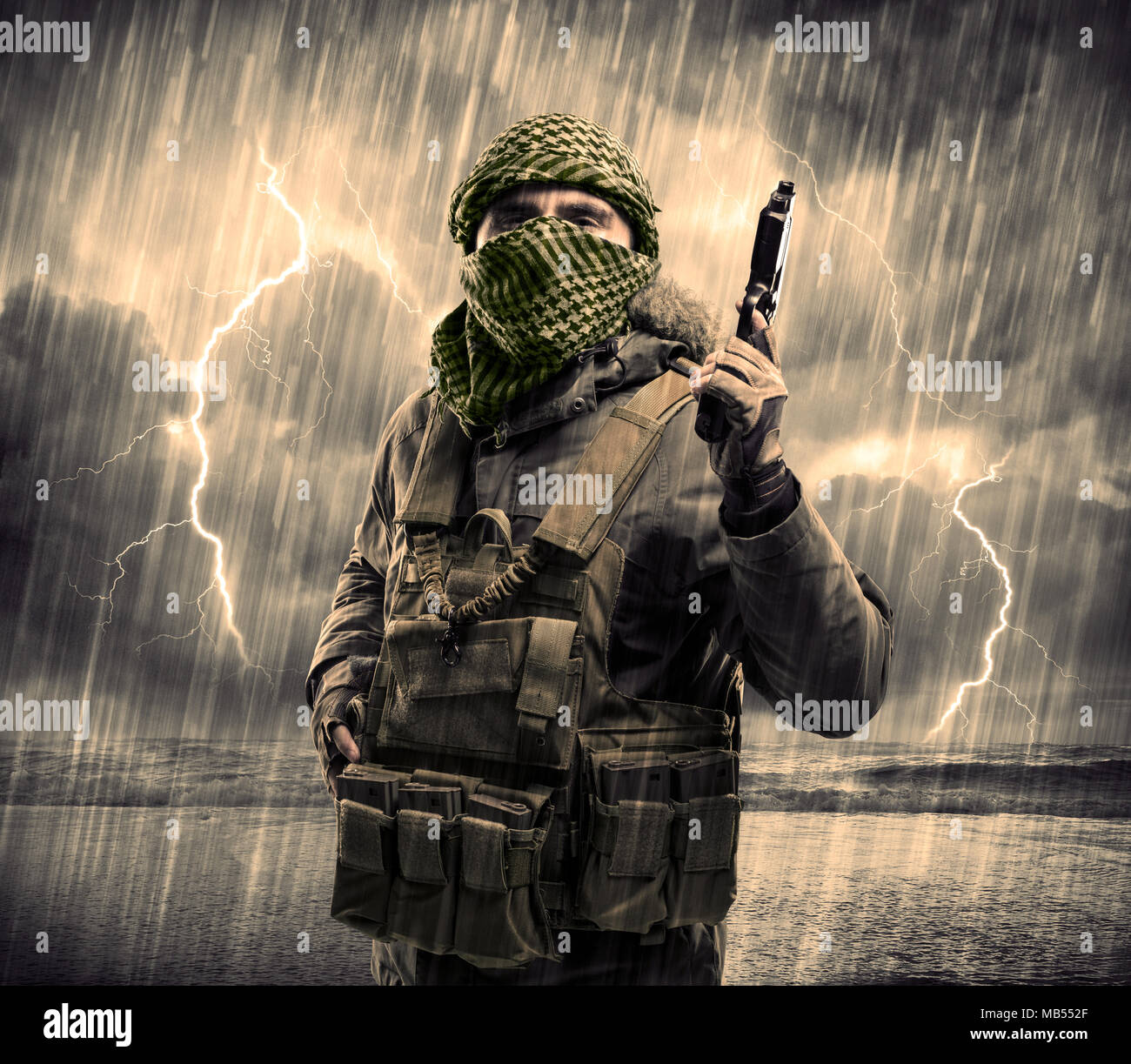 Portrait of a dangerous armed terrorist with mask and gun in a thunderstorm with lightning - Stock Image