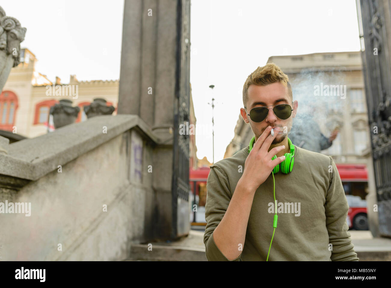 Young handsome man with green headphones and sunglasse enjoying a cigarette in the street. - Stock Image