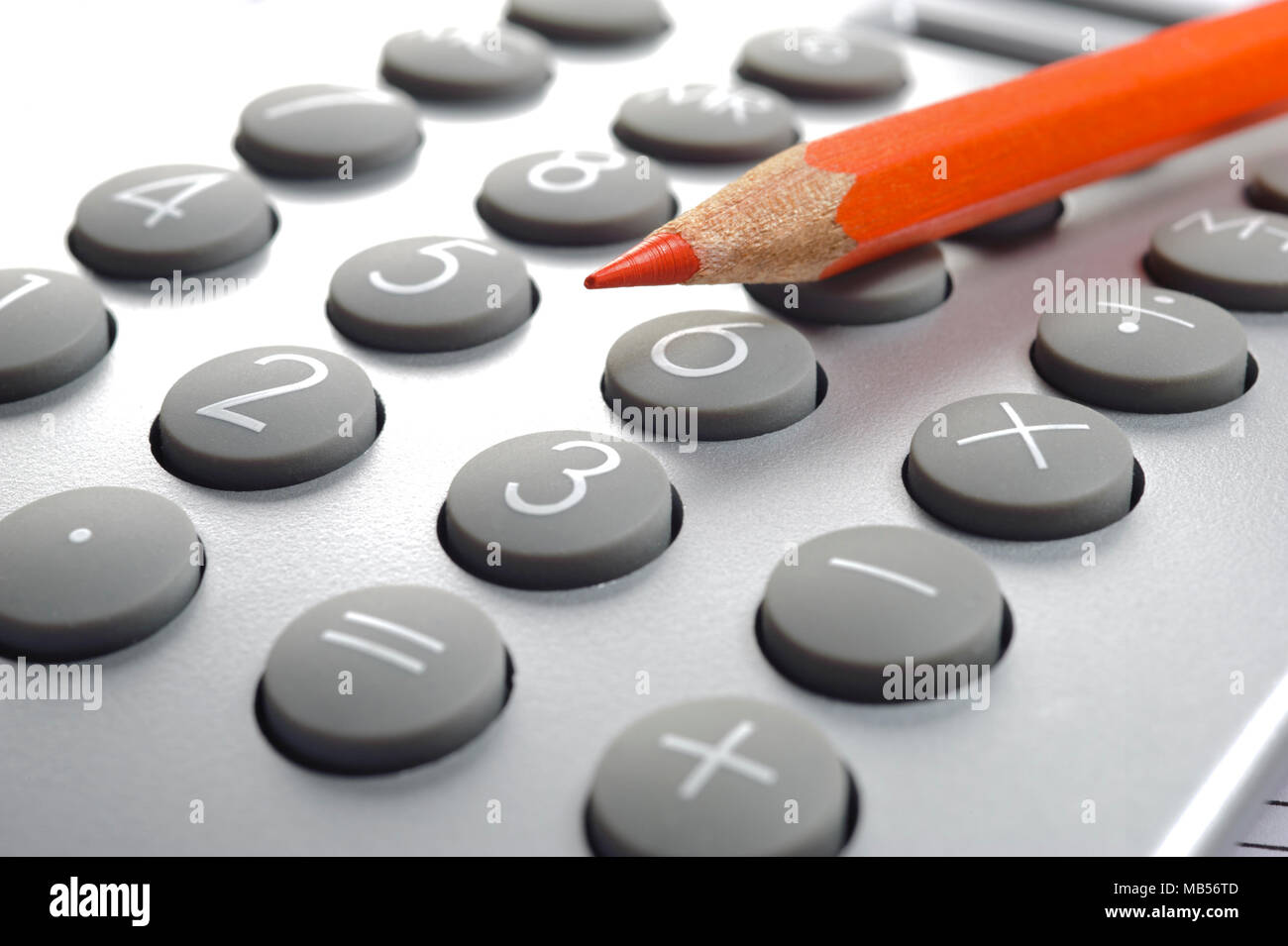 red pencil laying on top of calculator Stock Photo