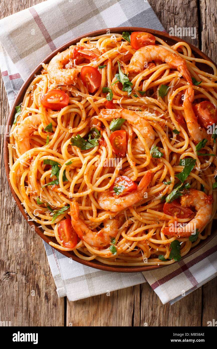 Italian pasta spaghetti with prawns, parmesan and herbs in tomato diavolo sauce close-up on a plate. Vertical top view from above - Stock Image