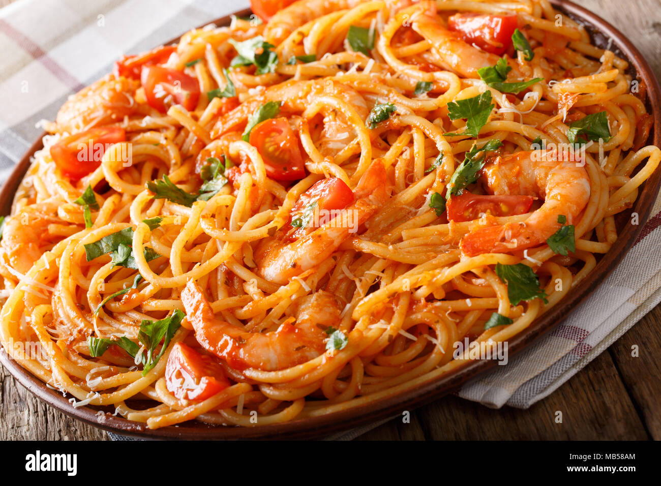 Tasty Italian spaghetti pasta with prawns, parmesan and herbs in tomato fra diavolo sauce close-up on a plate. horizontal - Stock Image