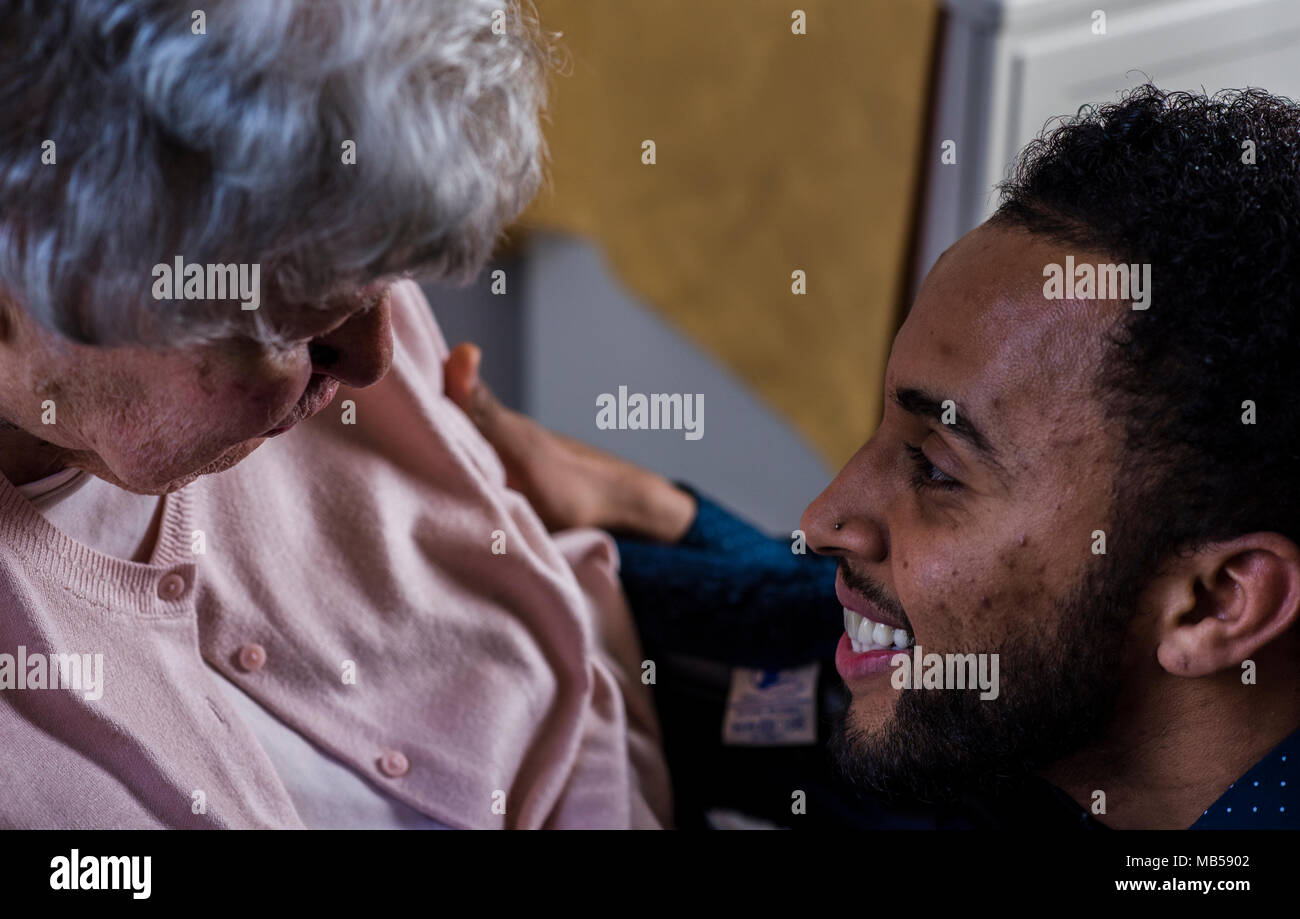 Cheerful care worker smiling towards 100 year old nursing home resident - Stock Image
