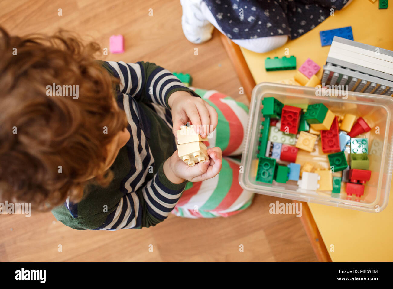 Child playing with colourful blocks in the kindergarten.Top view. - Stock Image