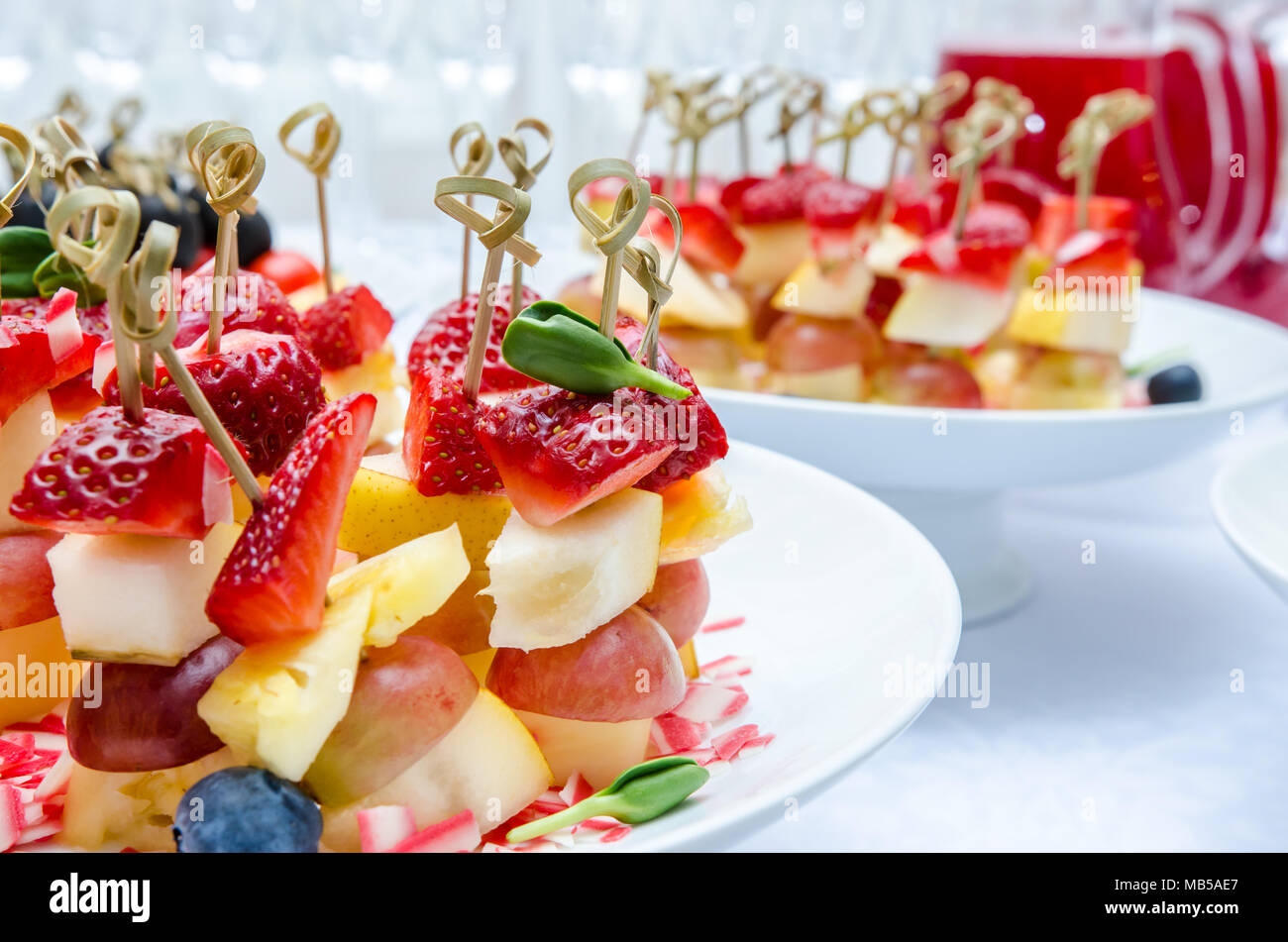 Set of delicious canapes with strawberry, pineapple, pear, blueberries and grape - Stock Image