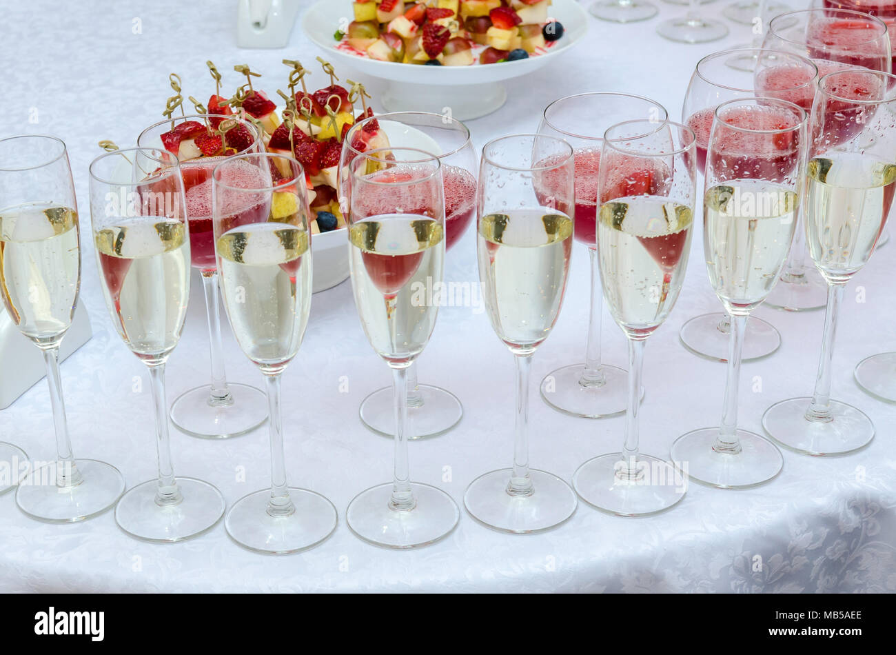 Champagne in the glases on the buffet table. Canapes with strawberry - Stock Image